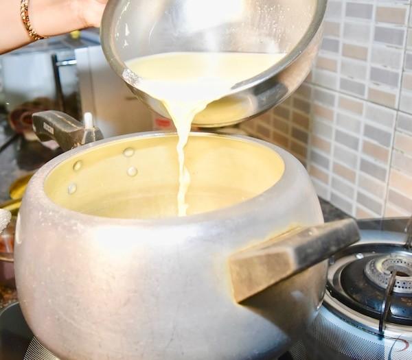 बेसन पेस्ट कुकर में डालते हुए Putting mixture in cooker